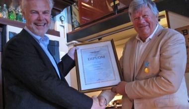 NLF's president Arild Solbakken (t.v) tildeler her NAK's gullmedalje med diplom